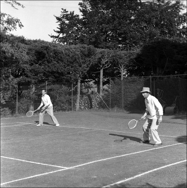 Two men taking part in a doubles tennis match at Crosslands House
