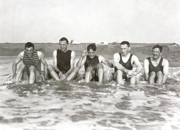 Five men sitting in the sea in their one-piece bathing suits. Four of them are smiling -- one looks more serious