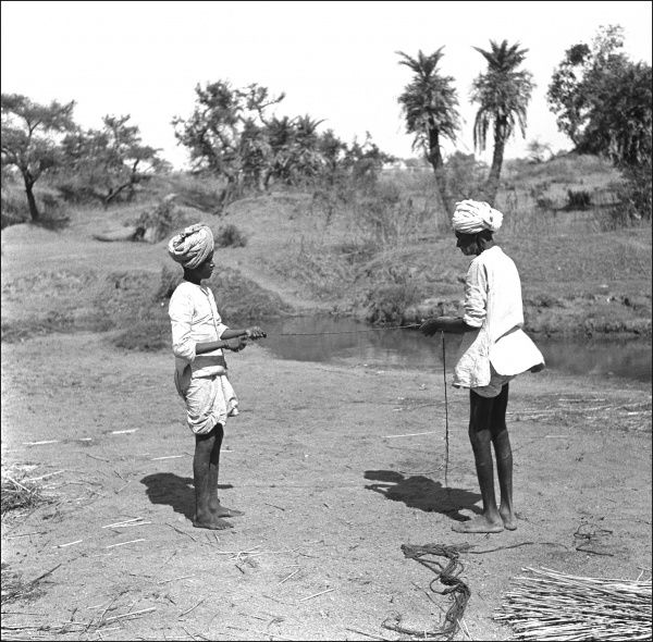 Two men working by a stream (in a former Indian province which now forms part of Modern Pakistan). They are tying up bundles of reeds. Photograph by Ralph Ponsonby Watts