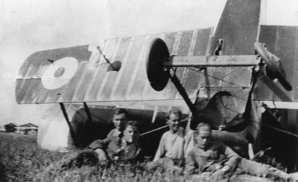 Four young men sitting in front of an upturned biplane in a field during the First World War. The plane has either crashed (there seems to be some minor damage) or overbalanced. Date: 1914-1918