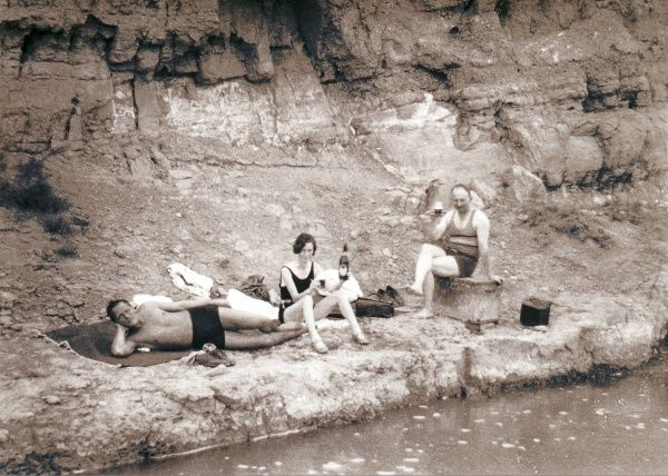 Two men and a woman, all in their bathing suits, enjoying a champagne picnic at the water's edge, with some rocks behind them