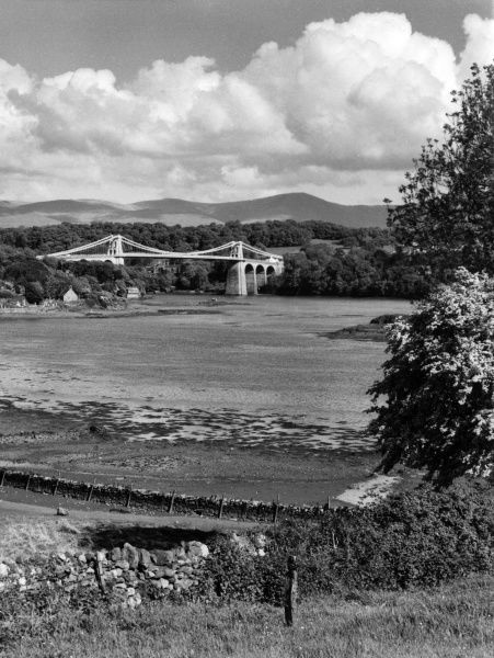 Thomas Telford's graceful suspension bridge over the Menai Straits, looking towards the Carnarvonshire mountains, Wales. Date: built 1819 - 1826