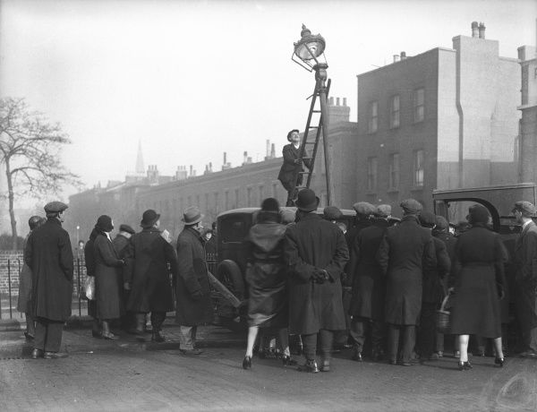 A crowd gathers to watch a workman up a ladder mending a broken lamp post, England