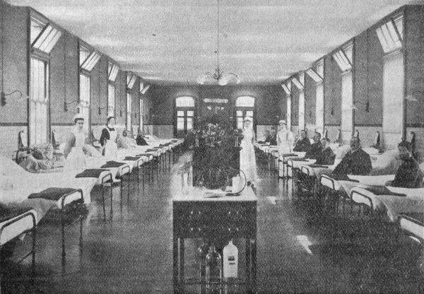 Men's ward at the parish of Islington's new 800-bed poor law infirmary opened in 1900 at Highgate Hill. Some patients are in bed while others are dressed and in chairs. Uniformed nurses are on duty. Date: 1905