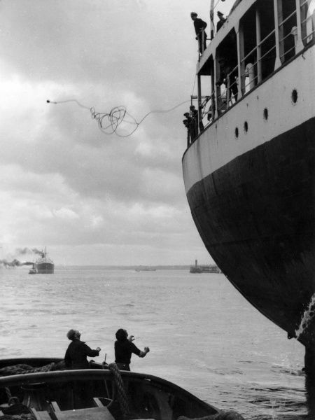 Heaving a stern line to a tug before proceeding down the River Mersey, Merseyside, England. Date: 1950s