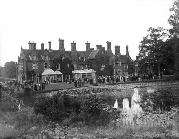 A garden party at Merton Hall, Norfolk, England. An Elizabethan mansion was completed by William de Grey in 1613 and the building was extended in the 19th century