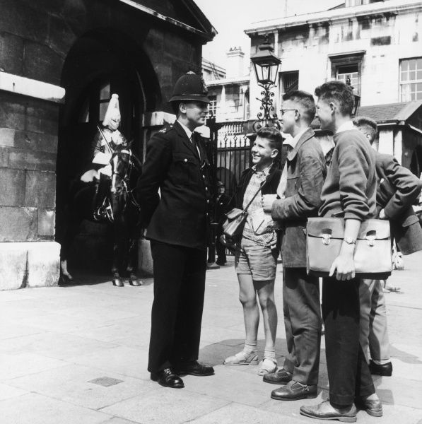 A Metropolitan Police officer speaking to a group of young tourists outside Horse Guards Parade in Whitehall, Central London