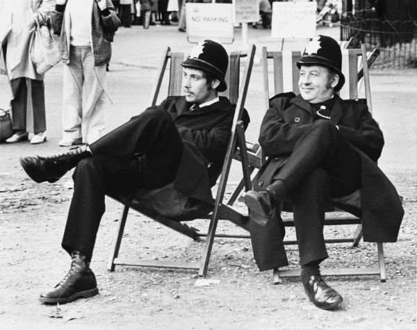 Two Metropolitan Police officers relax on deckchairs in The Mall, Central London, waiting for a political demonstration over the Grunwick dispute to begin
