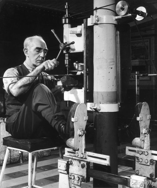 A wonderful photograph showing a metalworker operating a drill using all four of his limbs