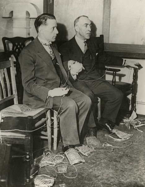 Undated photograph showing the method of linking up hands and feet of sitting mediums by means of electrical control. This is one of series of photographs documenting Harry Price's investigations into the mediumistic abilities of the brothers Rudi