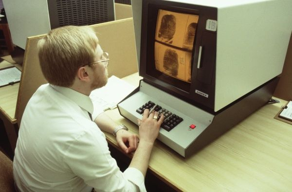 A man sits at a monitor to look at fingerprints on the Metropolitan Police database