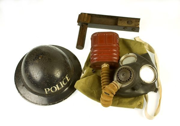 A Metropolitan Police gas mask, bag, rattle and tin helmet, as used in wartime