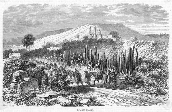 Travelers approach the town along the cactus-lined road