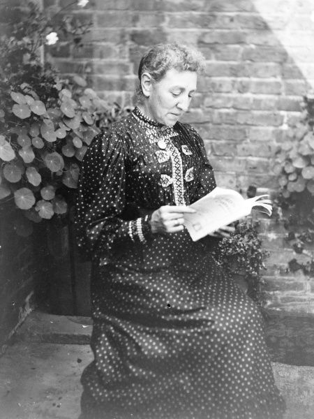 A middle aged woman sitting reading in a garden, Mid Wales. She is wearing a full-length spotted dress