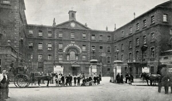 Entrance to the Middlesex Hospital, Mortimer Street, London. A group of onlookers, mostly children, stand at the gates. A hansom cab stands alongside. Date: 1908