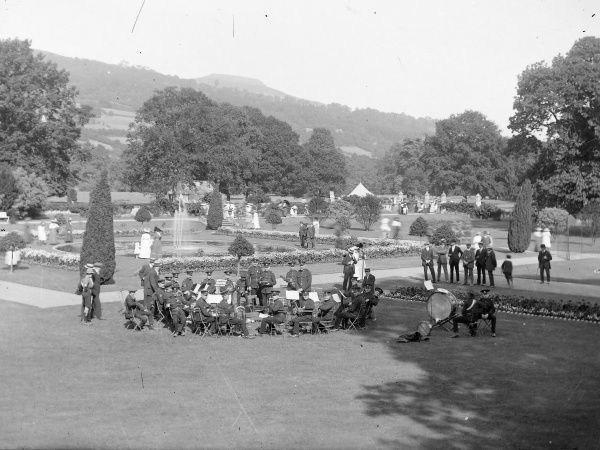 A military band in the grounds of a large country house in Crickhowell, Powys, Mid Wales. Various civilians are walking around, enjoying the gardens and fountain