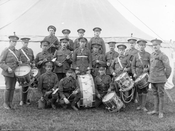 A military band, the Brecknockshire Battalion South Wales Borderers, together with their instruments, including six drums, posing for their photo in front of a tent
