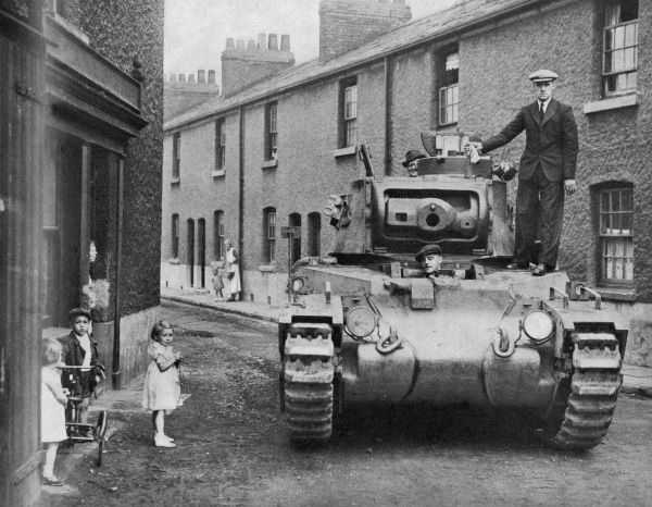 A photograph of a tank lookin out of place parked between rows of terrace houses. Residents of the street are posed along side it