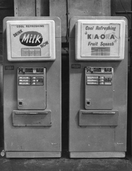 Two cold drinks vending machines standing side by side, one for cool refreshing milk, the other for cool refreshing Kia-Ora fruit squash. The machines look a little battered, which doesn't make the drinks seem very appetising. The price per drink carton