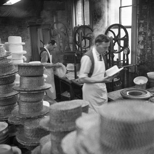 Two men work on the production of 'Straw Boaters' in the sweating room of a Milliner in York Street, Luton, Bedfordshire, England