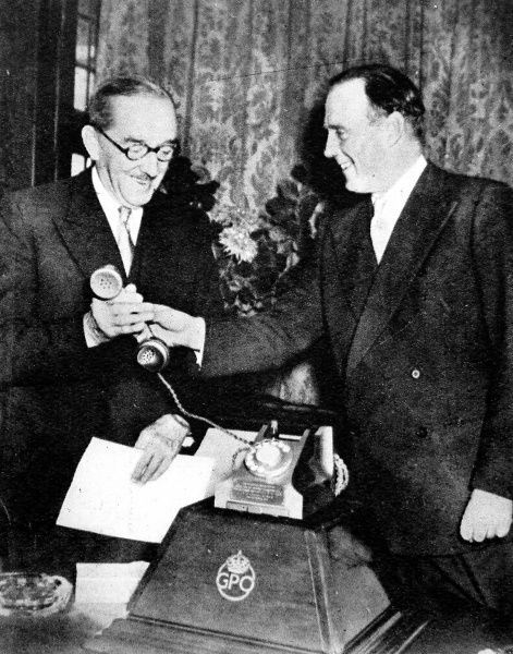 The postmaster general, The Earl de la Warr (right), presents to the constable of the Tower (Lord Alanbrooke), the 2,000,000th telephone installed in London in 1954