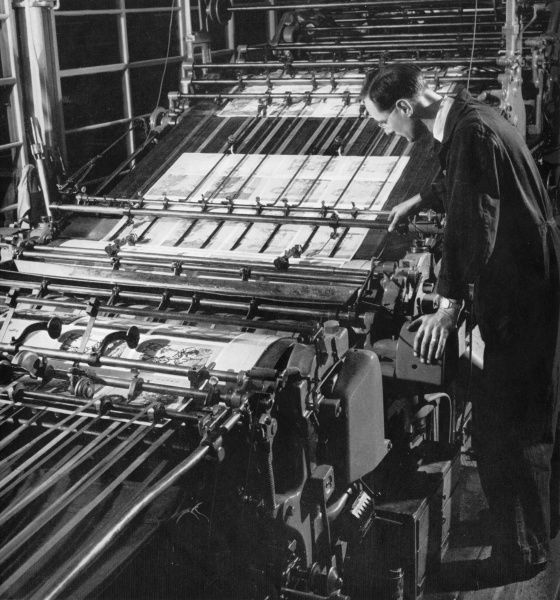 The Minder of a quad medium two-colour Letterpress Machine checks his sheet into the grippers at the Lund Humphries Printing Works. Photograph by Heinz Zinram