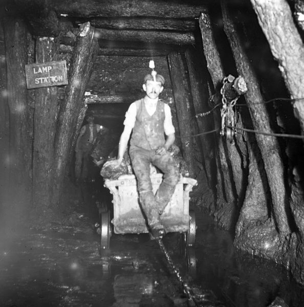 A miner riding a 'journey' of drams (coal trucks) at Tirpentwys Colliery near Pontypool in South Wales. Date: 1910