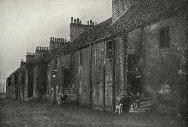 A row of decaying miners' cottages at Blantyre, a mining district to the east of Glasgow. A few residents stand at their doorways and children and dogs are at the steps below. Date: circa 1936