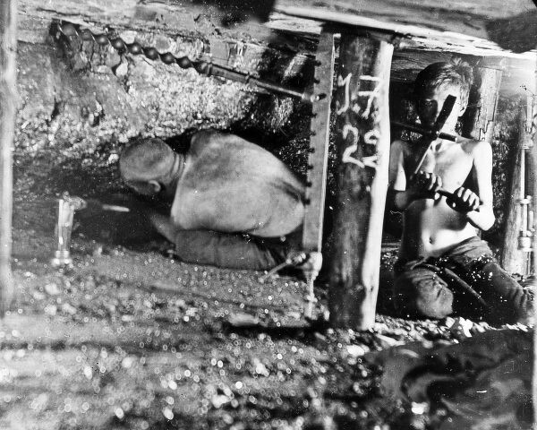 Two miners, one of them quite young, working in a narrow coal seam in a mine in South Wales