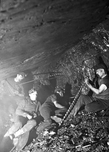 A group of miners working in a narrow coal seam in a mine in South Wales