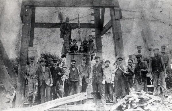 A group of men at Hook Colliery, near Haverfordwest, Pembrokeshire, South Wales. They are the current shift of miners plus the owner, standing near a wooden headframe connected to a mineshaft