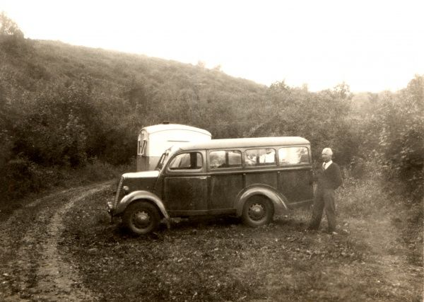 A man poses beside a mini van for transporting a number of passengers and a caravan on a hillside in an unidentified part of the UK during the 1930s