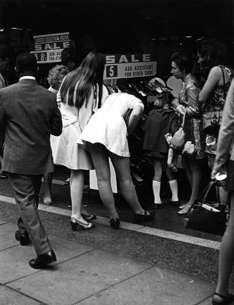 The dangers of bending over in a mini dress at the Summer Sales! Date: late 1960s