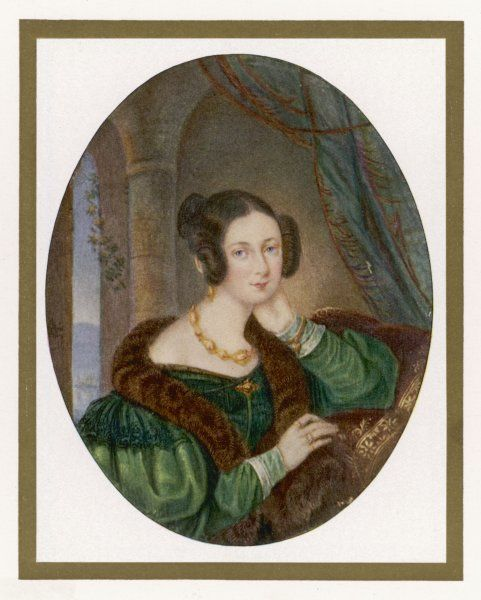 A young brunette woman wears a dark green dress with gigot sleeves with mancherons & white transparent cuffs. Also a brown fur tippet & gold necklace & brooch