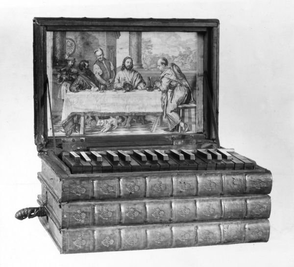 This miniature organ, enclosed in a folio of old books, has a painting of the supper at Emmaus inside its lid. Date: 1930s