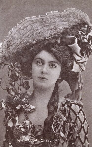 Stage Actress Miss Ethel Christine - a vry pretty young girl in a very large and elaborate hat, that is positively dripping with floral decoration. circa 1910s