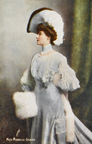 Mabelle Gilman wears a lace trimmed high-necked gown with a 'pouched' bodice, bell shaped flaring skirt, a fur- trimmed hat with a cocked brim & a fur muff & stole