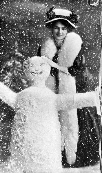 A Christmas scene with Miss Lily Elsie, actress, making a snowman in the snow