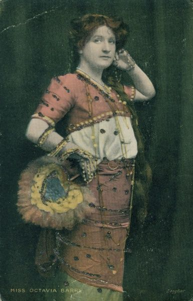 An almost full-length portrait of Miss Octavia Barry, a popular singer, in a colourful costume, with a feather fan in her hand. Date: early 20th century