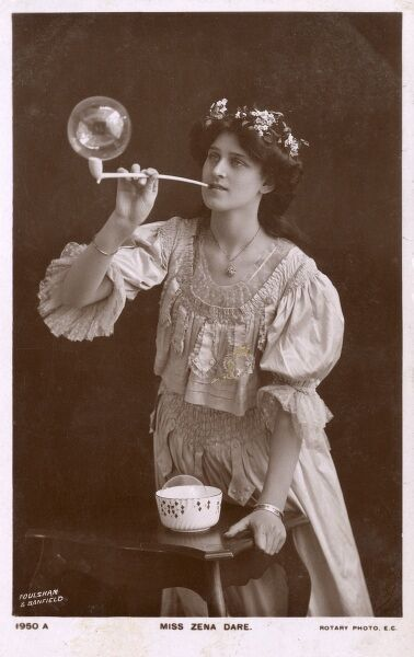 Miss Zena Dare (Actress) blowing a large bubble out of a long clay pipe Date: 1905