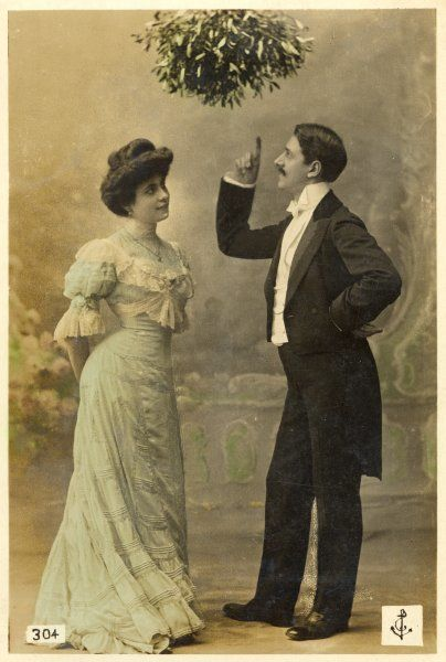 A gentleman treats a lady to a brief lecture on the significance of mistletoe ; she wonders when he will move from theory to practice
