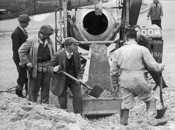 Workmen mixing concrete in a cement mixer. The cement and sand are put into a hod, which the travels up rails and is tipped into the revolving mixer