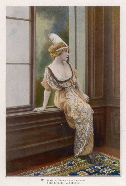 Mlle. Yane in a gown by Drecoll: round fur-trimmed decolletage, high waistline, draped skirt giving the effect of panniers & with panels of an ornate floral fabric