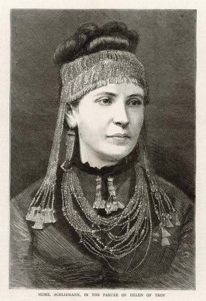 Mme Schliemann, wife of archaeologist Heinrich Schliemann, flaunts any pretence of preservation by openly wearing the ornaments found by her husband at Troy