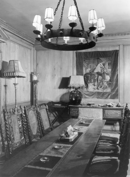 A formal, Medieval style dining room, with a mini wall tapestry, wooden chairs with barley twist backs and an ornate ceiling light. Date: 1930s