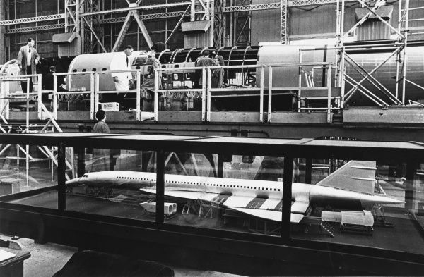 A model of the first prototype Concorde 001 stands in a glass case, close to the main assembly area (of the real aeroplane) at the St. Martin plant of Sud-Aviation, France. Date: 1967