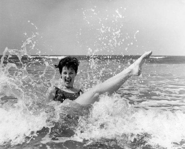 A model (Gill Emberton) pictured messing about i the seaside surf