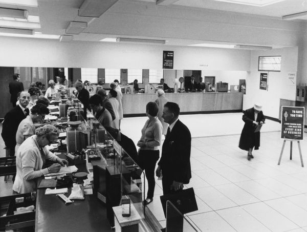 The ultra-modern post office at Eastbourne, Sussex, England, where a sign reads: 'To save you time, every counter clerk now deals with every kind of business'. Date: 1960s