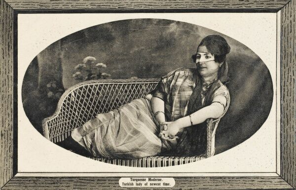 A 'Modern' Turkish veiled woman reclining on a wicker couch. The beginning of modern Turks
