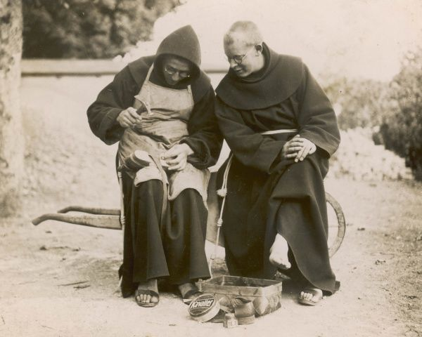 Monks from the Franciscan monastery of Gorheim, Germany. One mends his sandals with a hammer while another watches